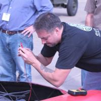 Testing the voltage of a battery at the Electric Car Conversion Conference in Cape Girardeau, MO.
